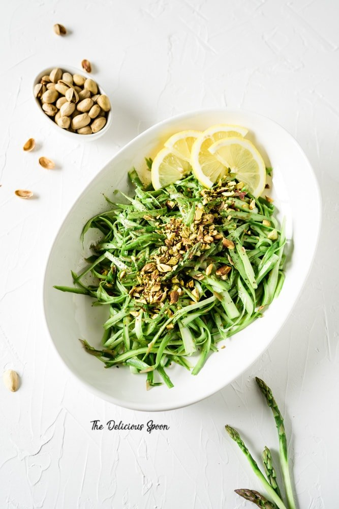 A bowl of asparagus and citrus salad with some pistachios on the side