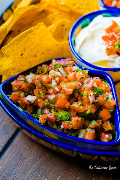 Close up of a homemeade Pico de Gallo in a blue Mexican style blue serving platter with nacho chips and sour cream