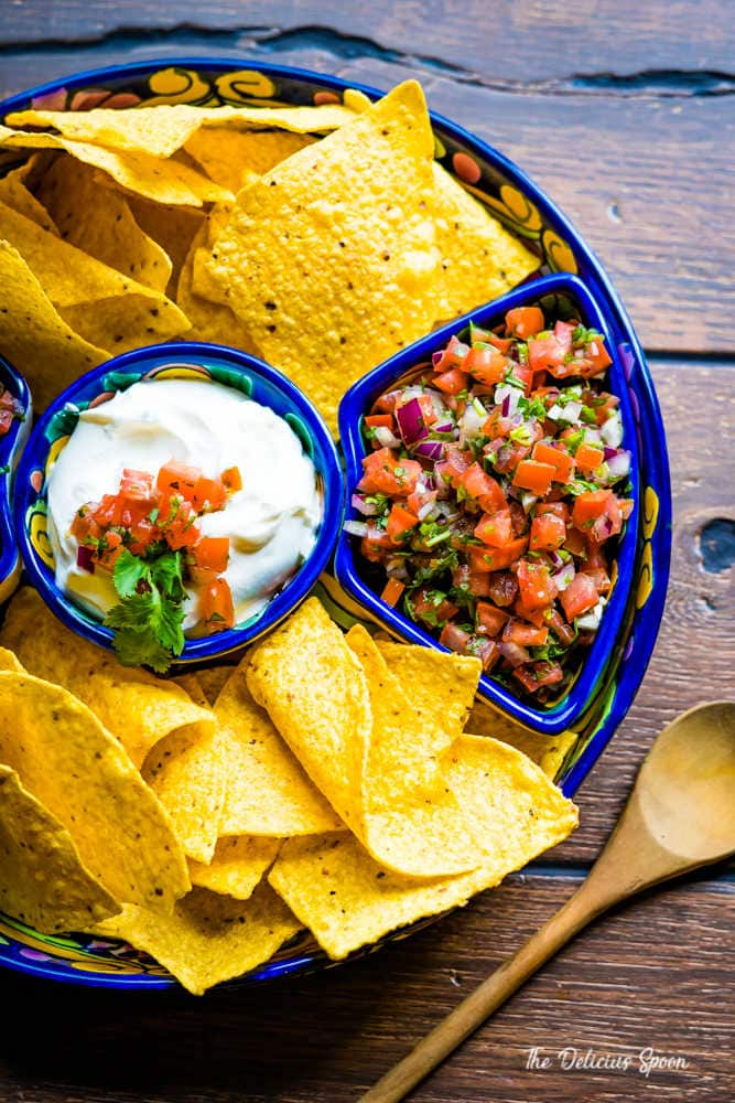 Overhead shot of a platter of nacho chips, sour cream and homemade pico de gallo inside a blue Mexican clay serving platter.
