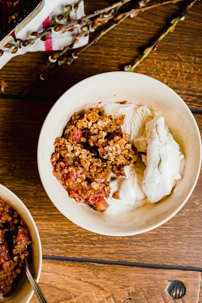 Overhead shot of Strawberry Rhubarb Crisp with vanilla ice cream in a cream coloured bowl on a wood table