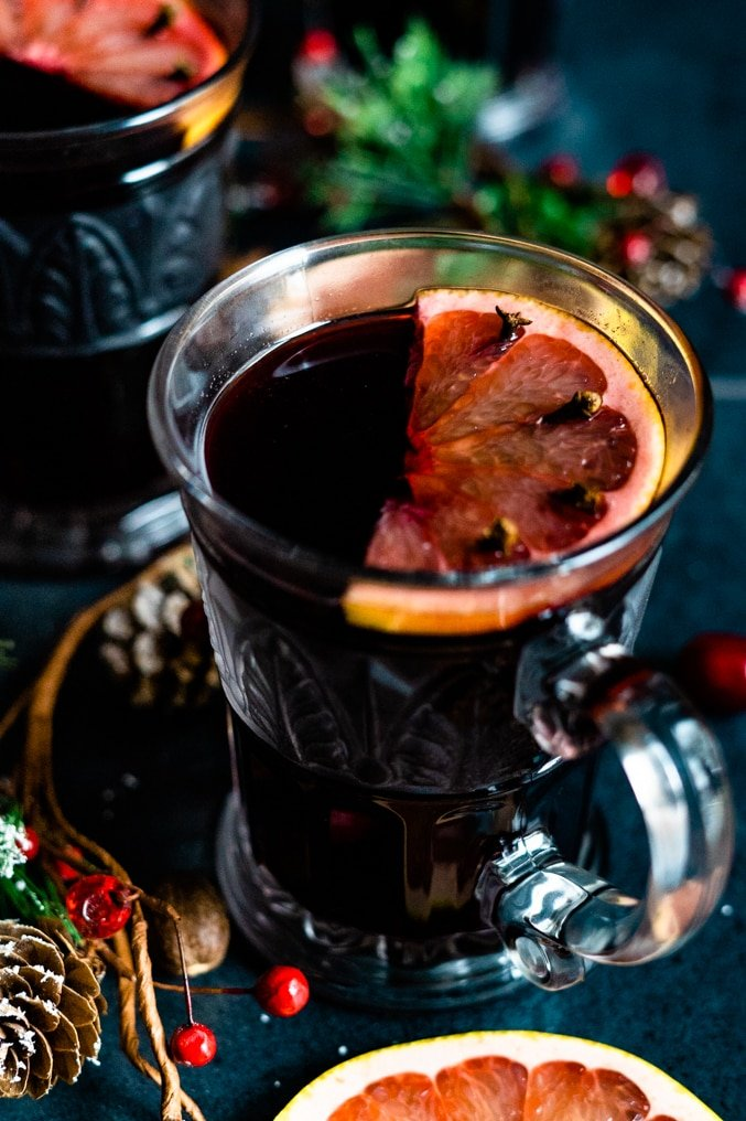 Peak into a glass of mulled wine decorated with a slice of grapefruit set on a holiday table.