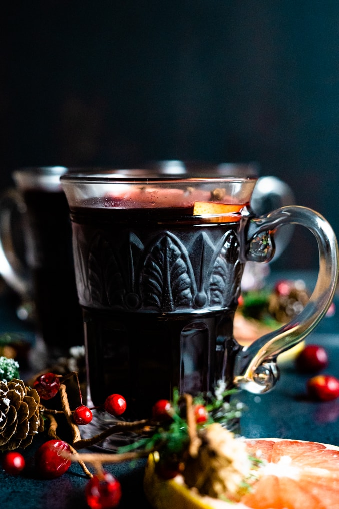 A mug of mulled wine on a black background surrounded by cranberries, pine cones and evergreen decorations.
