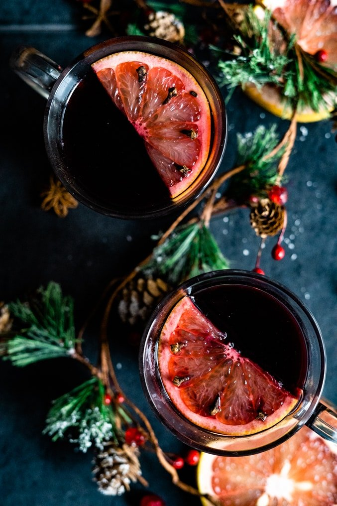 Overhead shot of two glasses of mulled wine shot on a holiday table decorated with ruby red grapefruit slices.