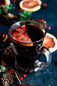 A glass of mulled wine decoraged with christmas greenery and grapefruits