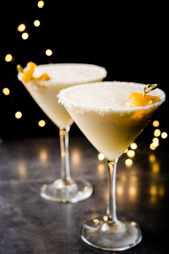 Two martini glasses filled with a frozen orange and coconut cocktail on a black background with twinkle lights