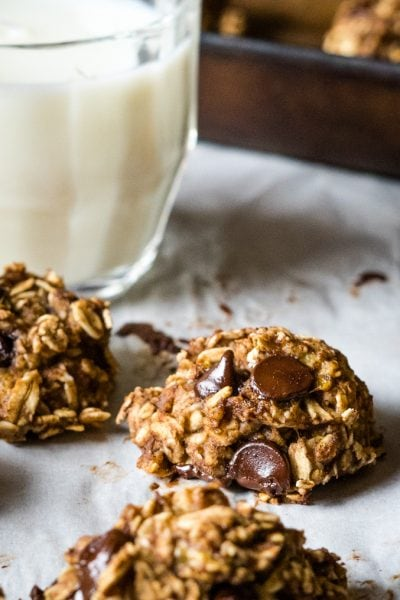 Three banana oatmeal chocolate chip cookies with a glass of milk