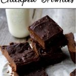A tall pinterest pin showing a stack of chickpea brownies cut in squares and a jug of milk