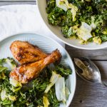 A table with two plats of roasted napa cabbage with kale and some chicken on a grey wood table with a white napkin