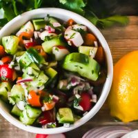 A colourful Fattoush Salad nestled in a white bowl surrounded by fresh veggies and lemon