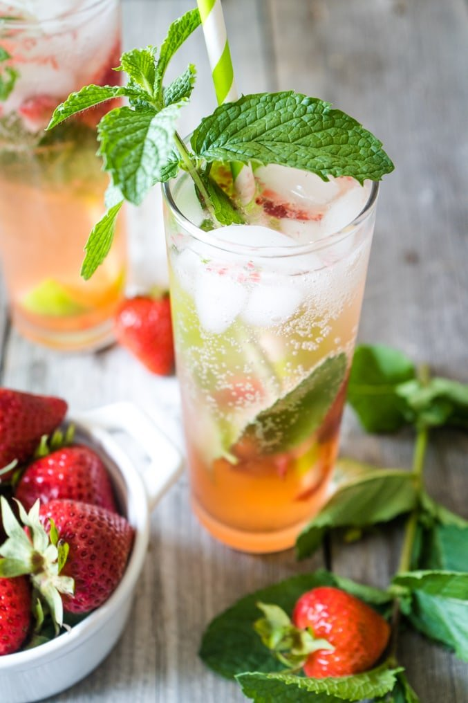 A low calorie strawberry mojito on a wood table topped with fresh mint