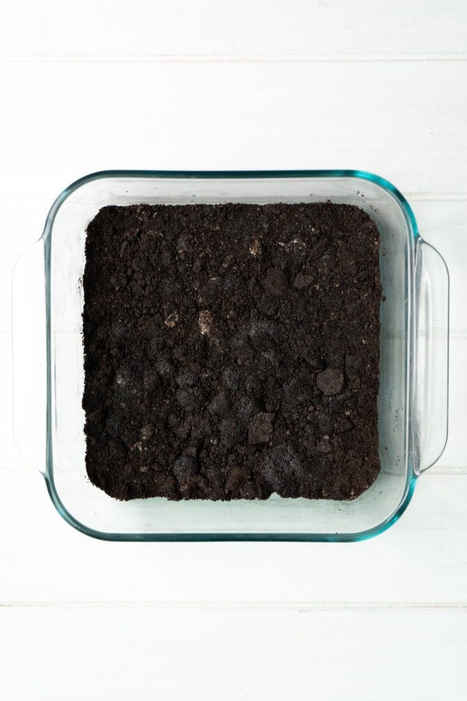A glass pan with an Oreo Cookie crust on a white table