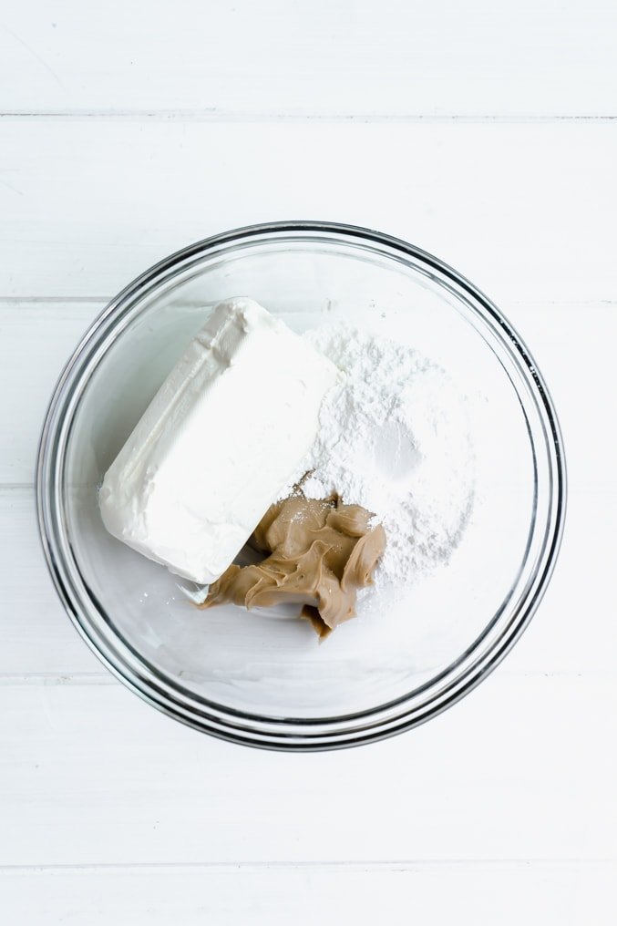 A glass bowl filled with a brick of cream cheese, icing sugar and peanut butter on a white table