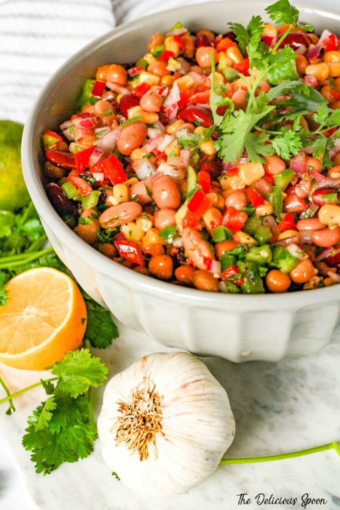 A big bowl of Mexican Bean Salad surrounded by garlic, cilantro and lemon