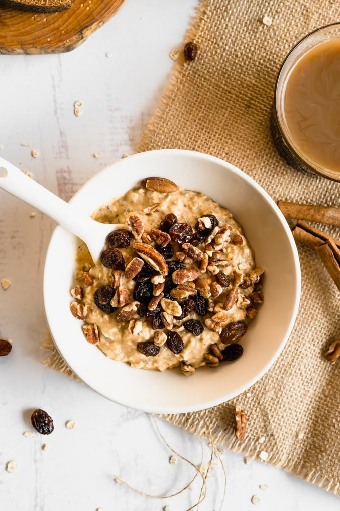 A bowl of overnight oats topped with pecans and raisins.