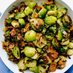 Pan seared brussel sprouts and bacon in a white bowl over a blue napkin