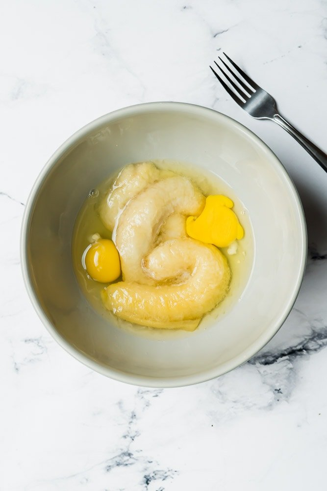 Process shot showing bananas and eggs in a large bowl for a healthy banana bread recipe