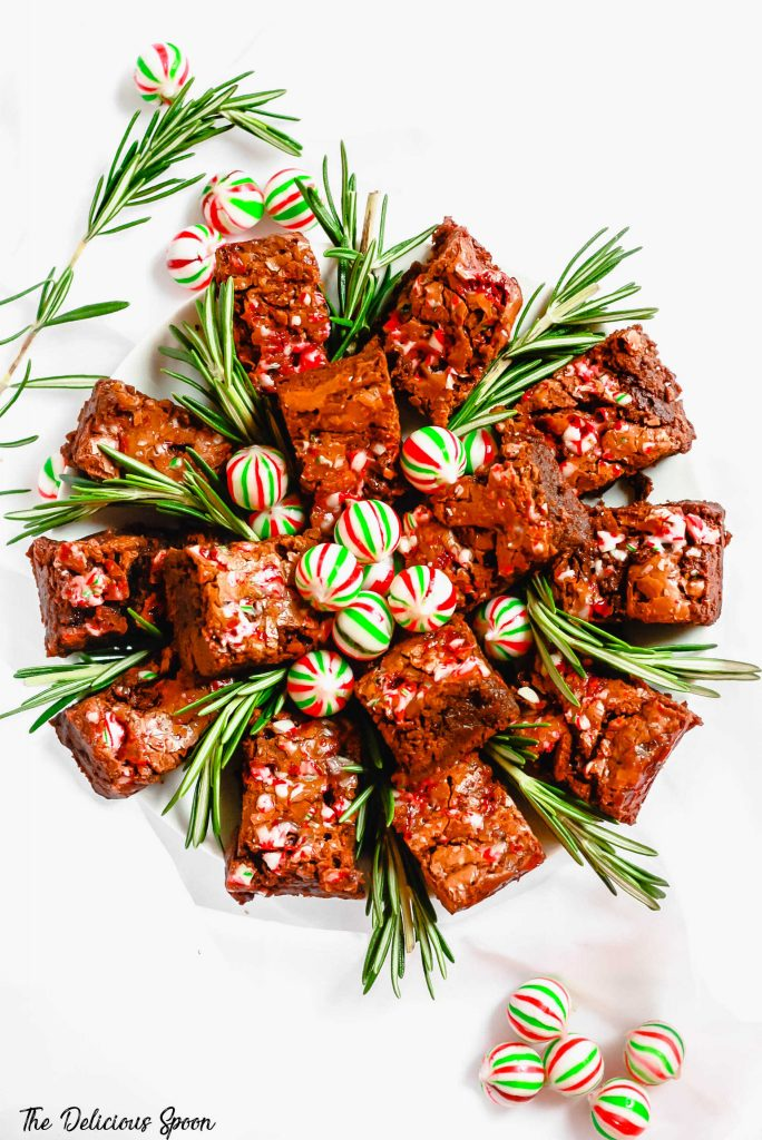 An overhead shot of a circular plate of peppermint brownies decorated with fresh rosemary and mints
