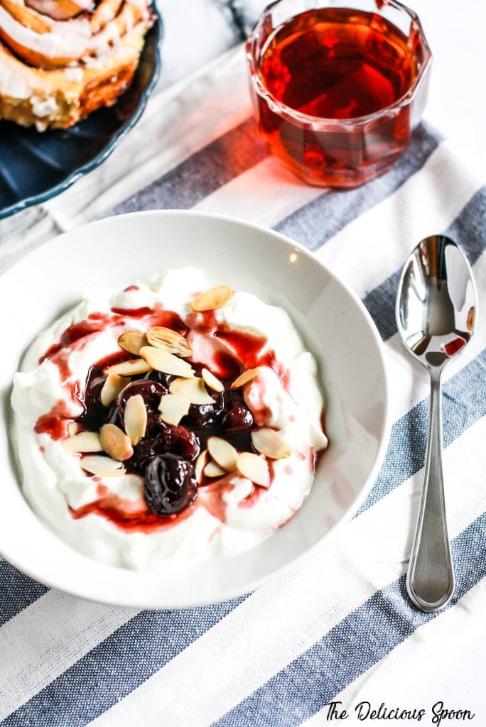 A bowl of greek yogurt topped with warm cherries