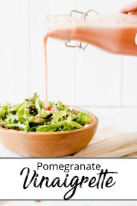 Bottle of pomegranate vinaigrette with two salads pinterest pin