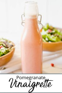 bottle of pomegranate vinaigrette with two salads pinterest pin2