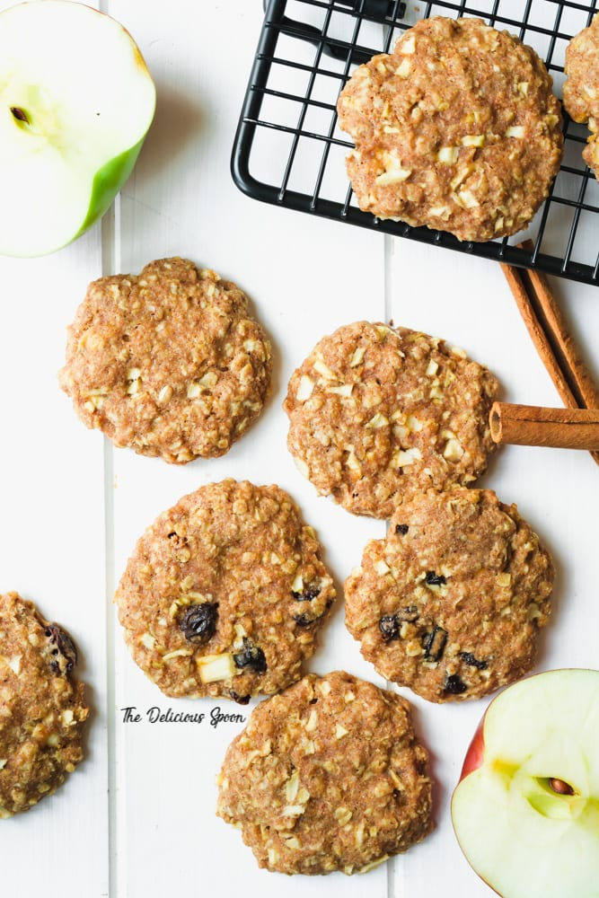 Overhead picture of apple oatmeal raisin cookies with some apples and cinnamon sticks