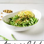 A pinterest pin showing a bowl of raw asparagus salad with pistachios