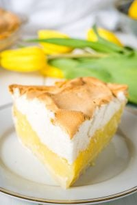 A head on shot of a slice of lemon pie with some yellow tulips in the background