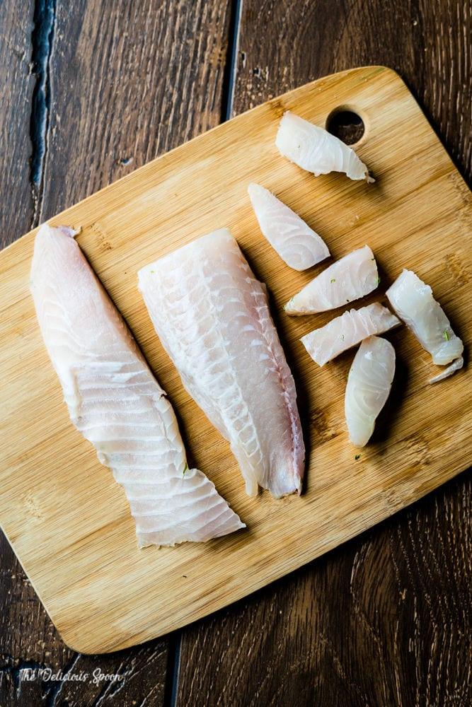 Raw white fish on a bamboo cutting board