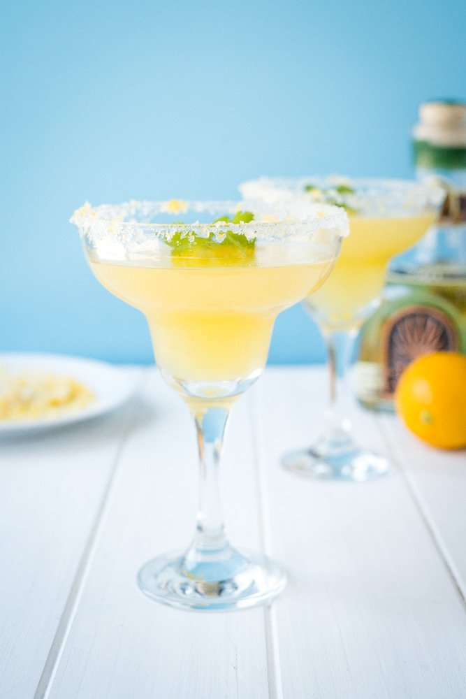 Two simple margaritas using the juice of Meyer Lemons in margarita glasses rimmed with salt, sugar and lemon zest.