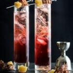 Two hibiscus cocktails in highball glasses on a dark background