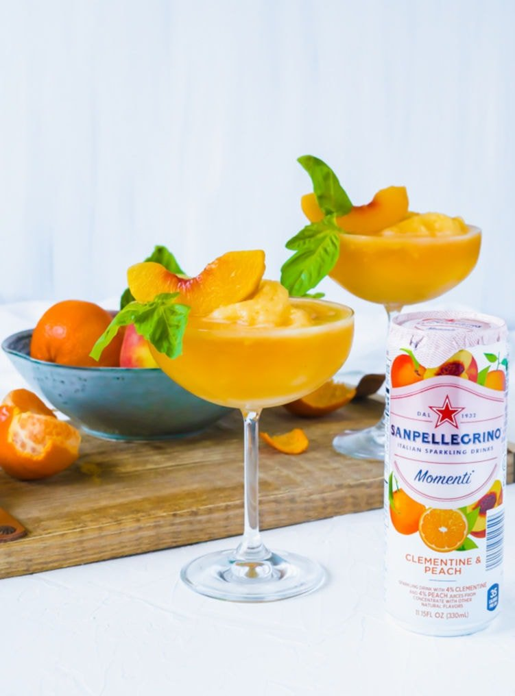 Two Frozen Peach Bellini Mocktails in champagne glasses decorated with a peach slice and basil leaf