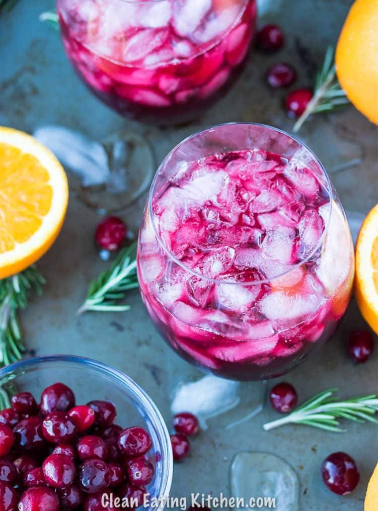 Overhead shot of a cranberry pomegranate citrus mocktail on a grey background with rosemary and cranberries sprinkled around
