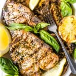 On overhead shot of a white platter of grilled pork chops decorated with grilled lemons and fresh basil leaves