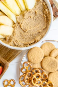 Close up of snickerdoodle dessert hummus with some apple slices for dipping on a wicker placemat