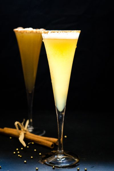 Two champagne flutes filled with apple cider and prosecco