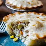 Close up of a turkey pot pie on a dark green plate with flaky pie crust