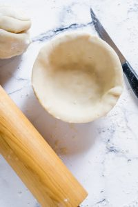 A pie tin lined with homemade pie crust with a rolling pin nearby