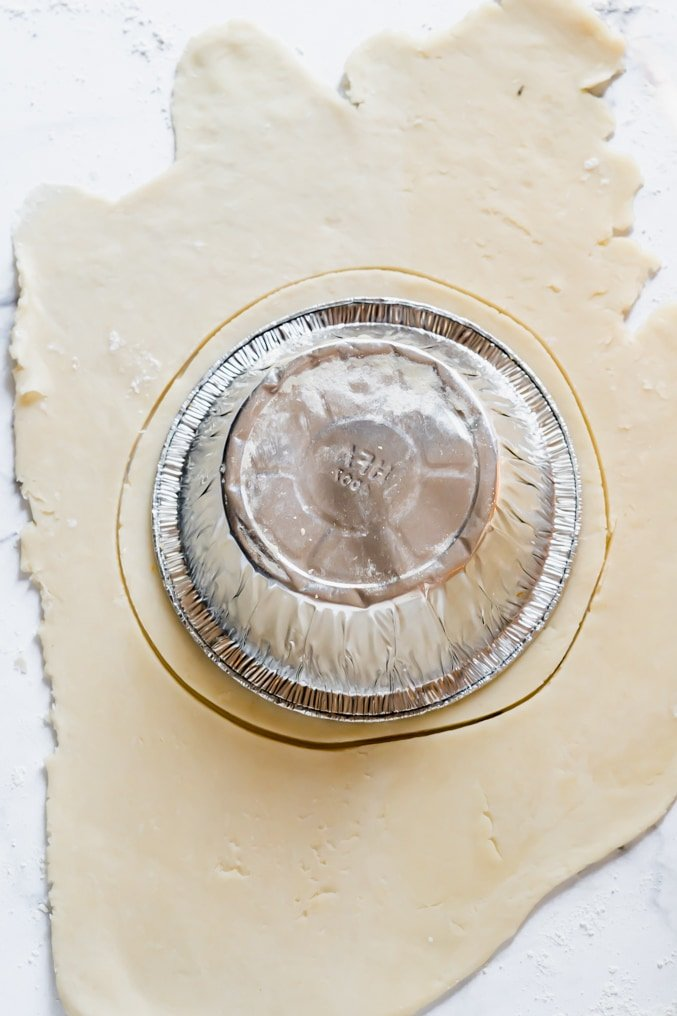 Homemade pastry rolled out with a pie tin on top and cut around the edge in a circle