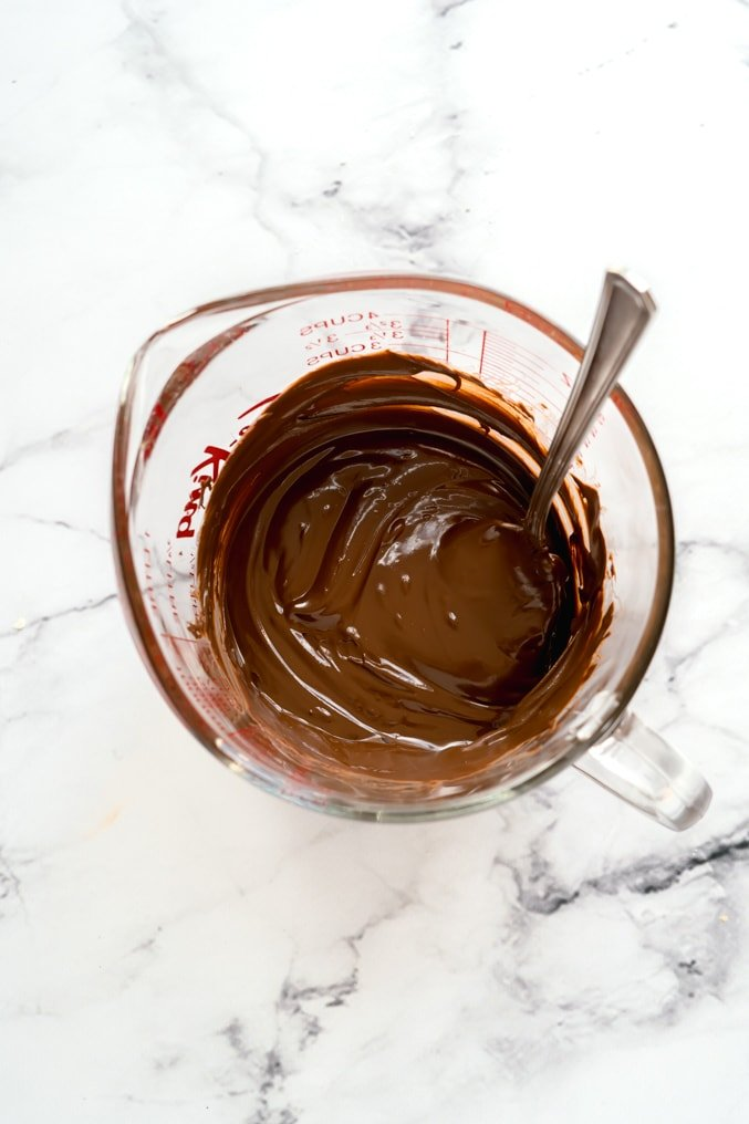 glass mixing bowl filled with melted chocolate and a spoon