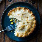 Overhead shot of a pot pie with a piece eaten and a fork on a dark green plate on a wood table