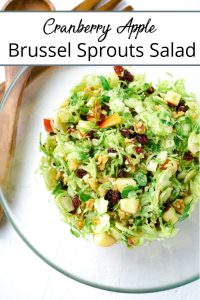 Pinterest pin of a brussel sprout salad in a glass bowl on a white table