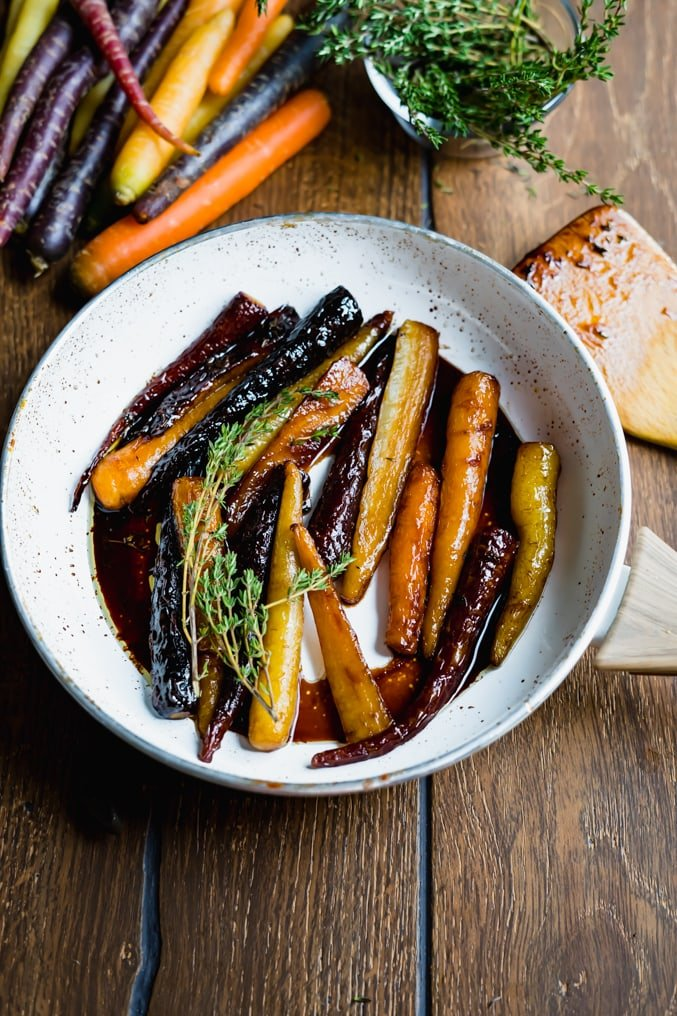 Pic of a white pan filled with honey glazed carrots on a wood table