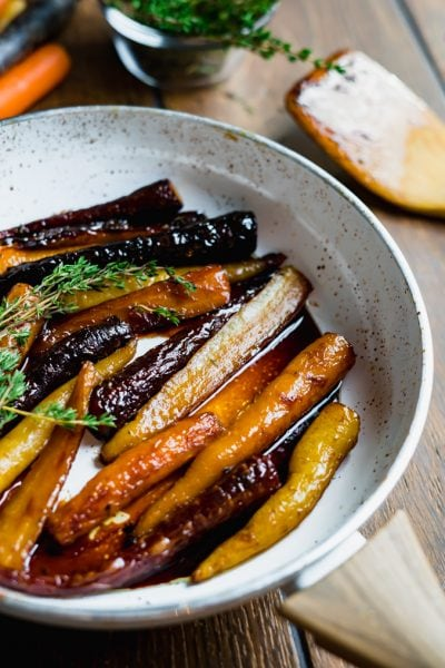 Close up of glazed heirloom carrots in a white pan on a wood table