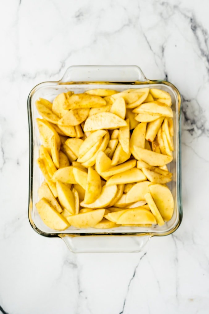 An 8 X 8 inch glass baking dish filled with seasoned apples on a white background