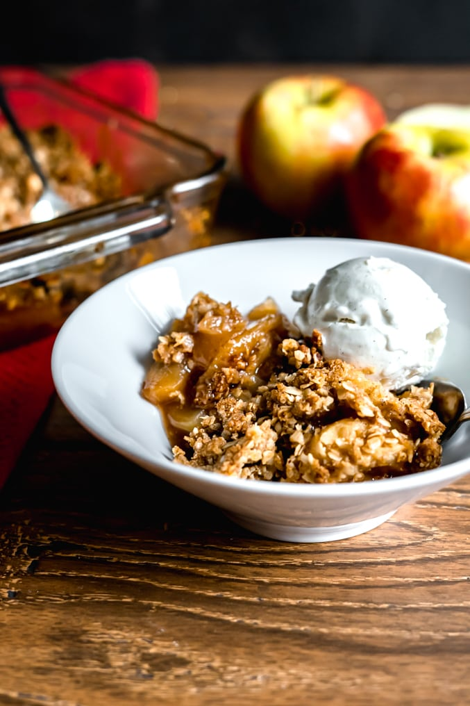A bowl of gluten free apple crisp with vanilla ice cream on a wood table with apples and the baking dish nearby