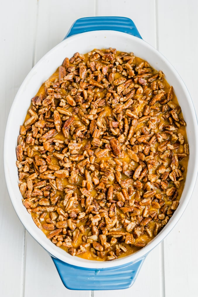 A blue dish filled with a casserole topped with pecans on a white table