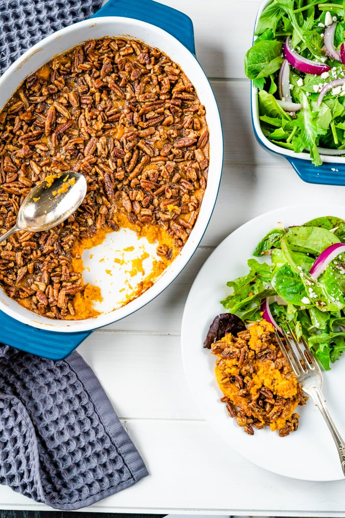 Overhead pic of a sweet potato casserole with pecan topping with a side salad nearby on a white table.