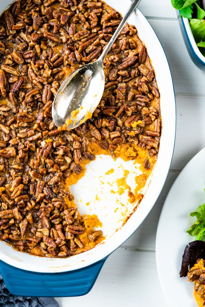 Overhead shot of a sweet potato casserole with pecan topping and silver serving spoon