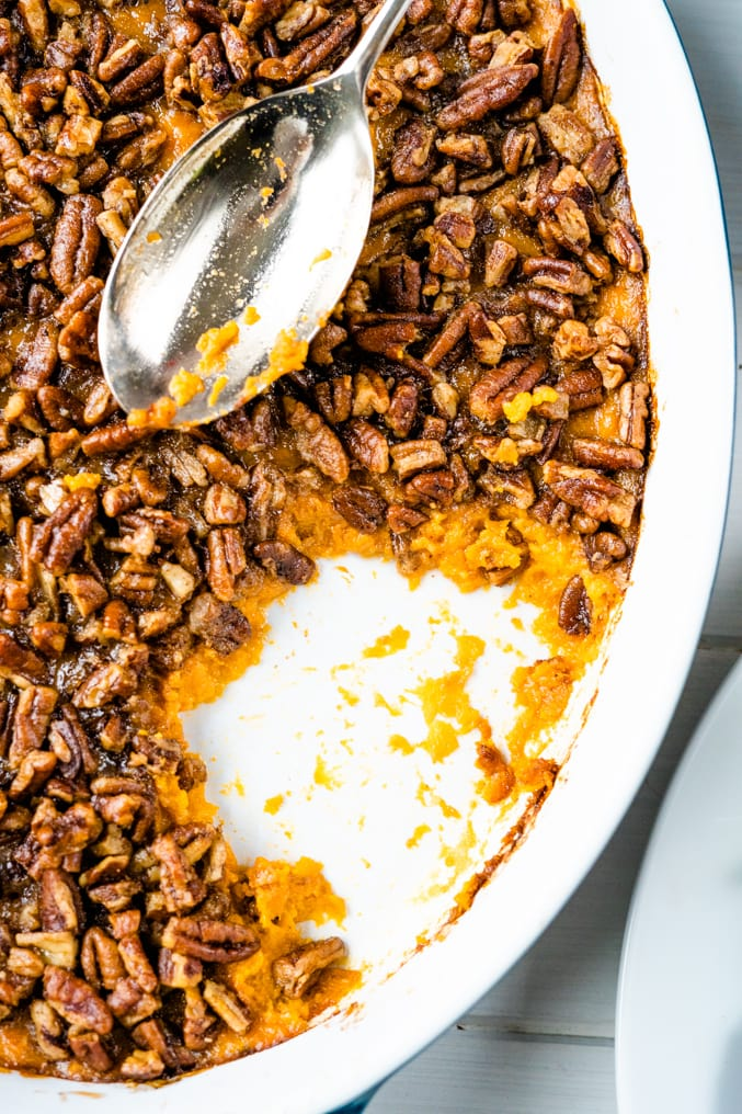 Close up of a sweet potato casserole with pecan topping with a spoon