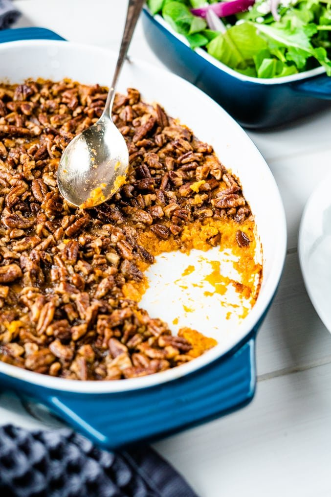 Close up of a sweet potato casserole with pecan topping with a silver serving spoon on a white table
